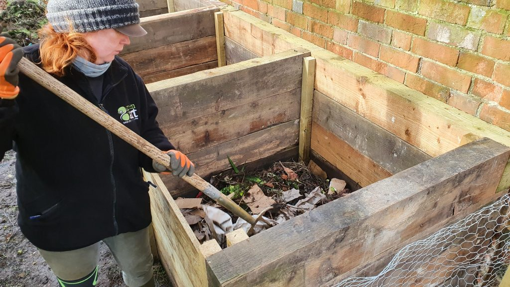 Photo of Jenny using a fork to turn the compost in a bin